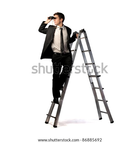 Young businessman on a ladder using binoculars - stock photo
