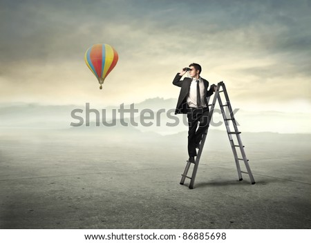 Young businessman on a ladder using binoculars and hot-air balloon in the background - stock photo