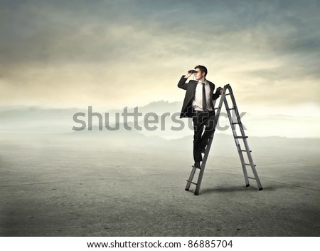 Young businessman on a ladder using binoculars in a desert