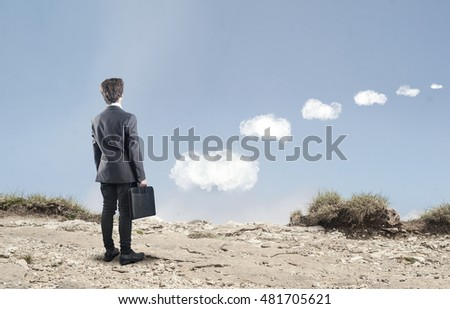 Young businessman on a mountain looking to an arranged path of clouds