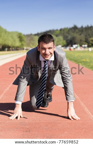 young businessman on a running track in summer - stock photo