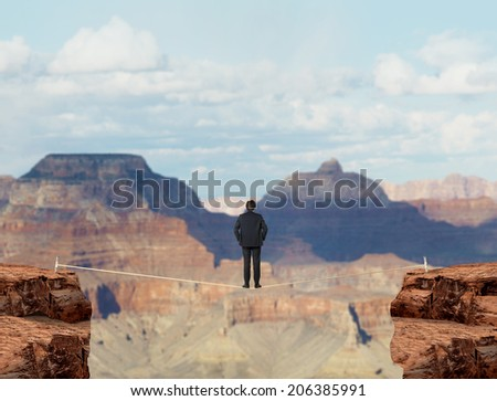 Young businessman on a suspended rope, red Arizona desert.  - stock photo