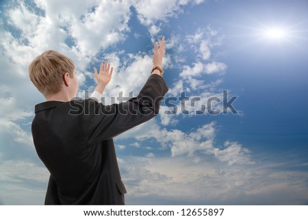 young businessman on background of sky asks from sun of success. - stock photo