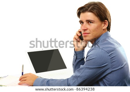 Young businessman on cellphone sitting in front of laptop isolated on white background - stock photo