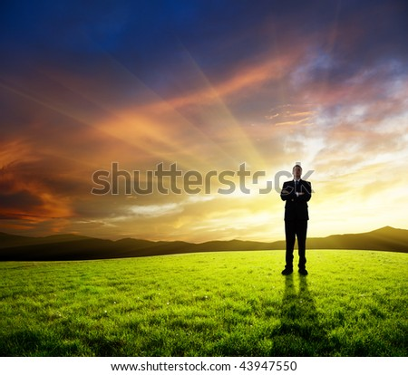 young businessman on green field and sunset - stock photo