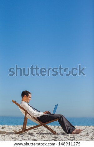 Young businessman on his deck chair using his laptop on the beach - stock photo