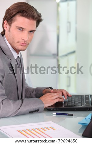 Young businessman on laptop - stock photo