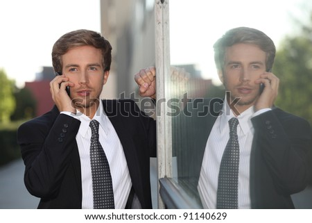 Young businessman on mobile phone - stock photo