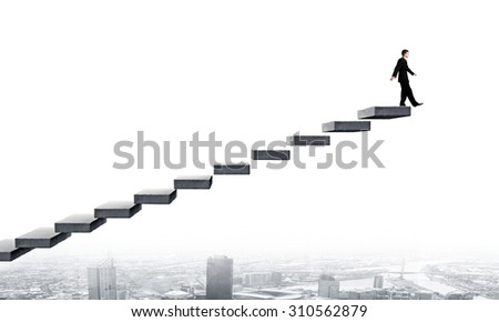 Young businessman on staircase top representing success concept - stock photo