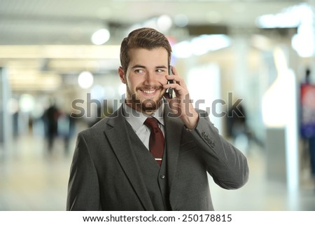 Young Businessman on the cell phone at the airport - stock photo