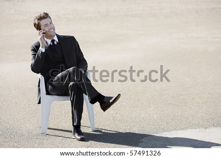 Young businessman on the phone at beach - stock photo