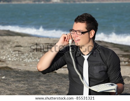Young businessman on the phone at beach
