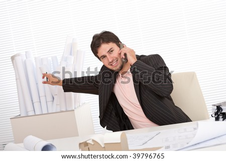 Young businessman on the phone at office