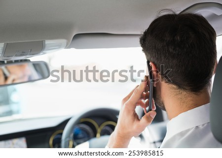Young businessman on the phone in his car