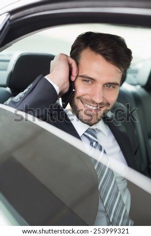 Young businessman on the phone in his car - stock photo