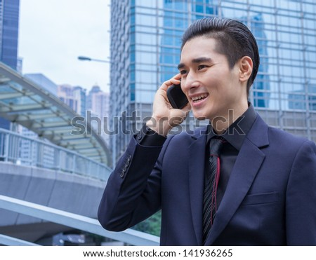 Young businessman on the phone in the city - stock photo