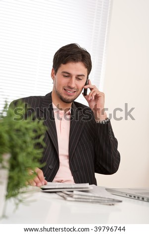 Young businessman on the phone working at office