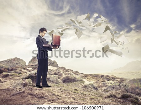 Young businessman opening a briefcase with paper sheets flying away from it - stock photo