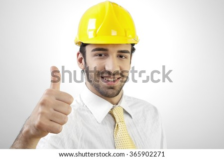 Young businessman or engineer is making OK sign in front of a grey background.