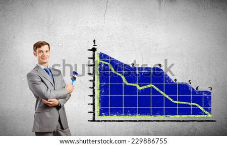 Young businessman painting graphs and diagrams with brush