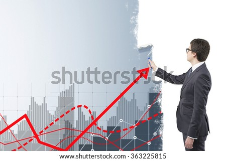 Young businessman painting grey bar charts and red graphs on a white wall with a roller. Side view. Concept of financial calculations.