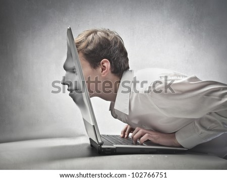 Young businessman passing his head through a laptop screen - stock photo