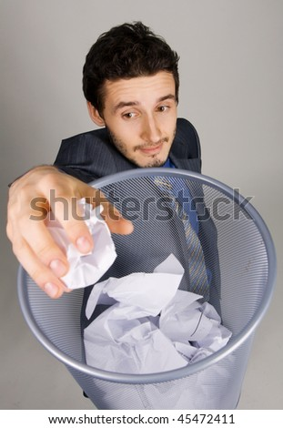 Young businessman playing basketball with crumpled paper - stock photo