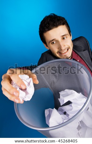 Young businessman playing basketball with crumpled paper, blue background
