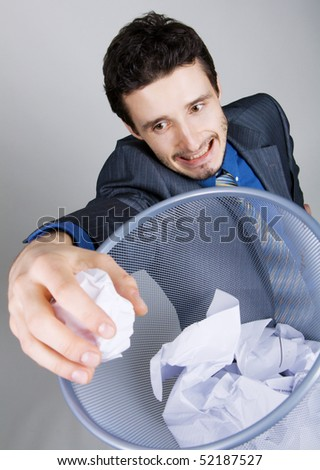 Young businessman playing baskteball with crumpled paper