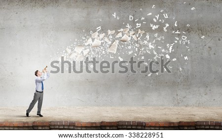 Young businessman playing flute and papers flying out - stock photo