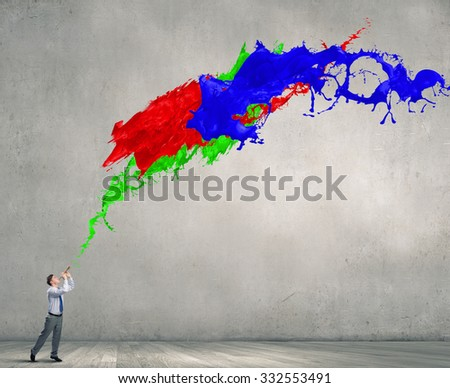 Young businessman playing pipe and colorful splashes coming out