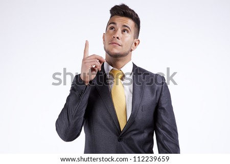 Young businessman pointing and looking up (isolated on gray - stock photo