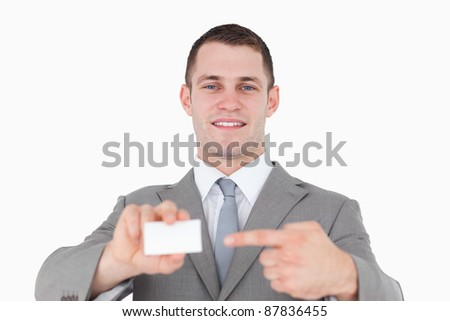 Young businessman pointing at a blank business card against a white background - stock photo