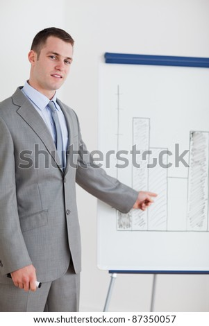 Young businessman pointing at chart - stock photo