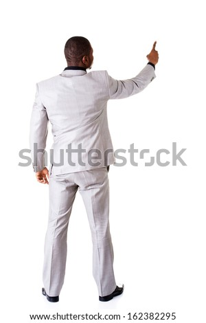 Young businessman pointing on copy space. back view. Isolated on white.