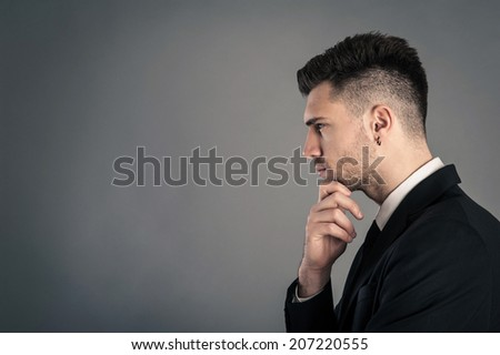 Young businessman portrait thinking against dark background. Conceptual image.