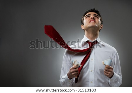Young businessman pray with blowing necktie and bunch of money. Please, help me in my business!