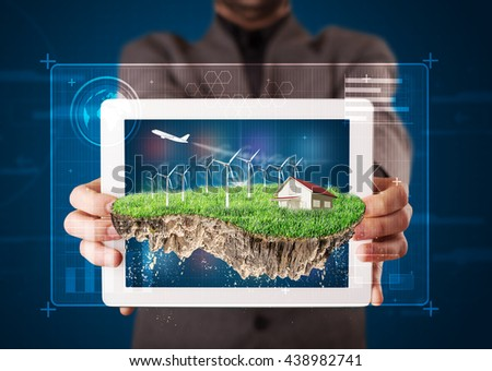 Young businessman presenting a perfect ecology land with a house and windmills - stock photo