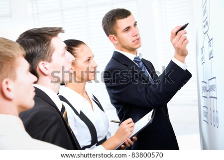 Young businessman presenting his ideas on whiteboard to colleagues - stock photo