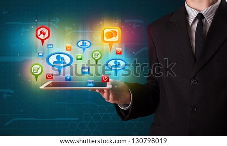 Young businessman presenting modern tablet with colorful social signs and icons - stock photo