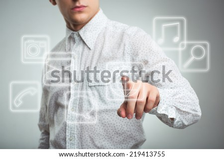 Young businessman pressing application button on computer with touch screen - stock photo