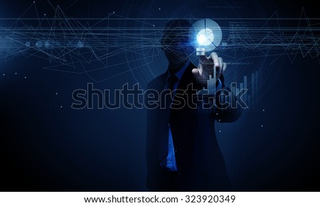 Young businessman pressing high tech circle icon on media screen - stock photo