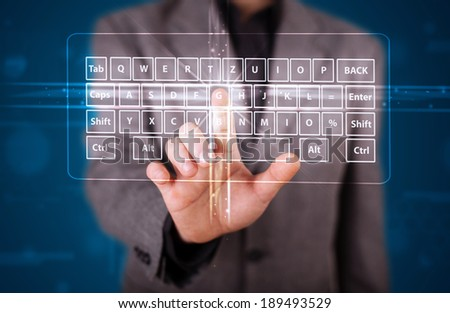Young businessman pressing virtual type of keyboard
