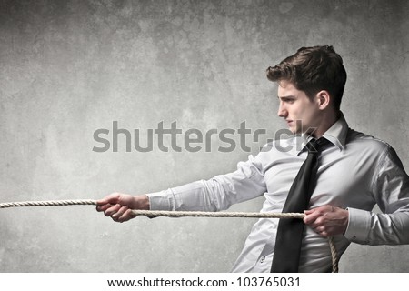 Young businessman pulling a rope - stock photo