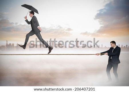 Young businessman pulling a tightrope for business man against cityscape on the horizon - stock photo