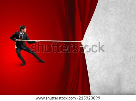 Young businessman pulling curtain with rope. Place for text - stock photo