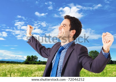 Young businessman raising his hands in sign of victory - stock photo