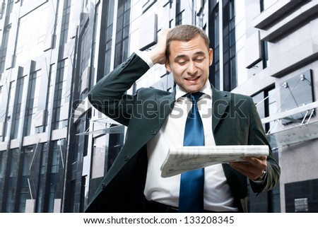 Young businessman reading a daily newspaper and holding his head - stock photo