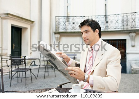 Young businessman reading a newspaper while sitting in a coffee shop's terrace table drinking coffee. - stock photo