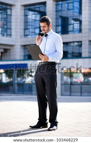 Young businessman reading document outside a building